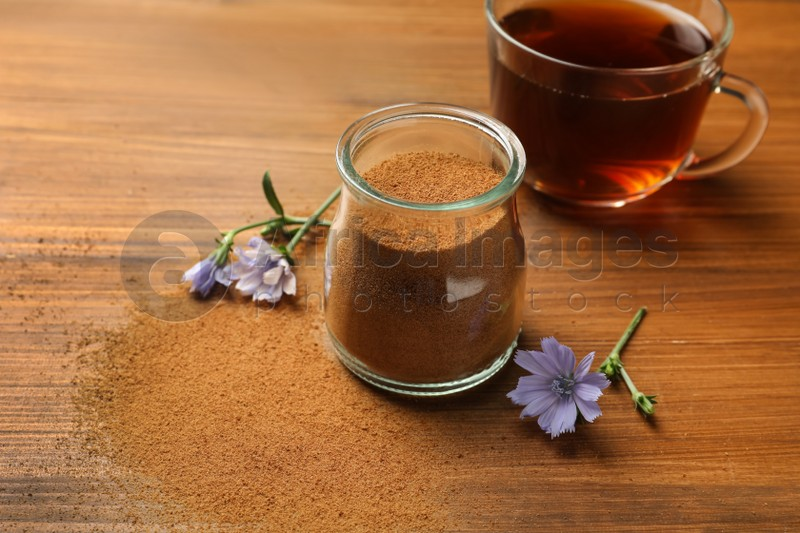 Jar with chicory powder, cup of delicious drink and flowers on wooden table
