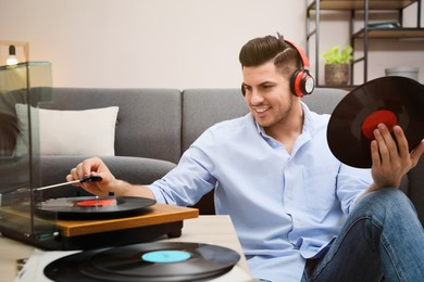 Happy man listening to music with turntable at home