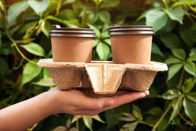 Woman holding cardboard holder with takeaway paper coffee cups outdoors, closeup