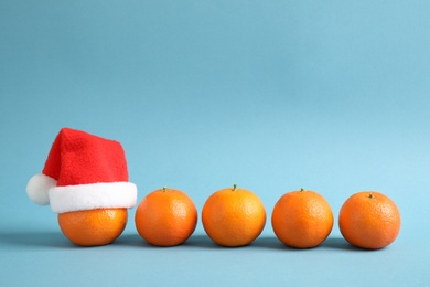 Row of fresh tangerines and one with Christmas hat against light blue background. Space for text