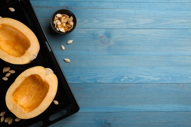 Halves of fresh spaghetti squash in baking sheet on light blue wooden table, flat lay with space for text. Cooking vegetarian dish
