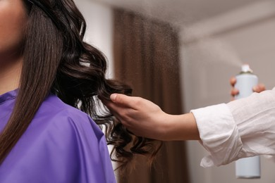 Stylist working with client in salon, making hairstyle