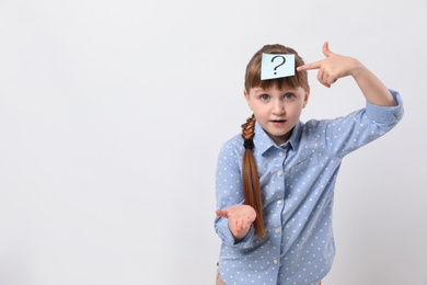 Pensive girl with question mark sticker on forehead against white background. Space for text