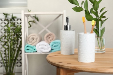 Holder with bamboo toothbrushes on table against blurred background