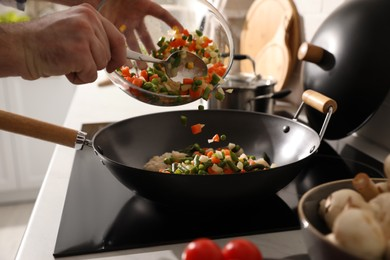 Man pouring mix of fresh vegetables into frying pan, closeup