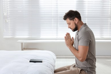 Religious man with Bible praying in bedroom
