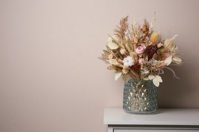 Beautiful dried flower bouquet in glass vase on white table near light grey wall. Space for text