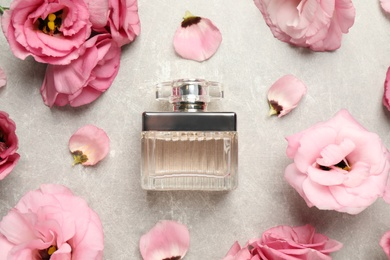 Flat lay composition with bottle of perfume and eustoma flowers on grey textured background