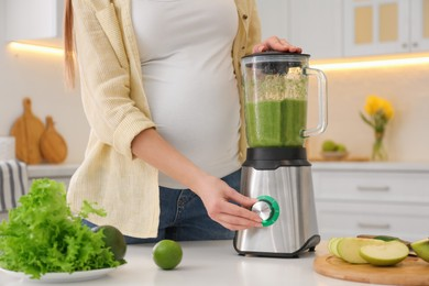 Young pregnant woman preparing smoothie at table in kitchen, closeup. Healthy eating