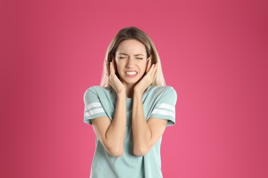 Emotional young woman covering her ears on pink background