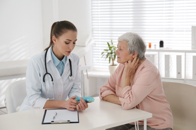 Doctor giving pills to senior patient in office