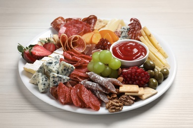 Plate of different appetizers with dip sauce on white wooden table, closeup