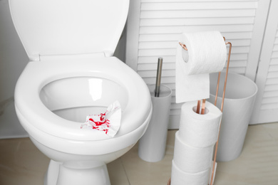 Sheet of paper with blood on toilet seat in bathroom