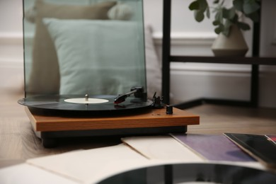 Stylish turntable with vinyl records on floor indoors