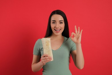 Happy young woman with tasty shawarma showing okay gesture on red background