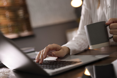 Woman working with laptop in office, closeup of hands