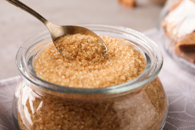 Taking spoon of brown sugar from glass bowl on table, closeup