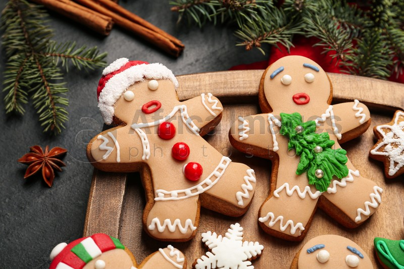 Delicious Christmas cookies, cinnamon and fir branches on black table, closeup