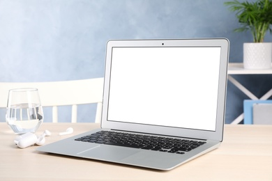 Modern laptop with blank screen on table indoors. Copy space text