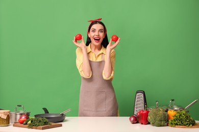 Young housewife with vegetables and different utensils on green background