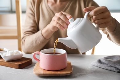 Woman pouring tea into ceramic cup at table, closeup