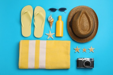 Flat lay composition with beach objects on light blue background