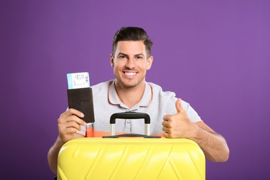 Handsome man with suitcase and ticket in passport for summer trip on purple background. Vacation travel