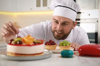Happy professional confectioner decorating delicious cake at table in kitchen