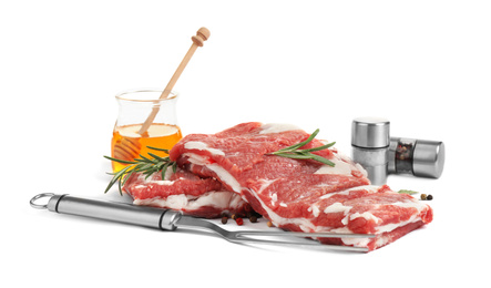 Raw ribs with herbs and pepper on white background