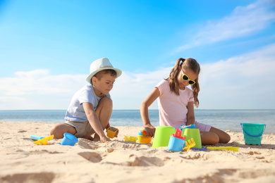 Cute little children playing with plastic toys on sandy beach