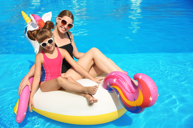 Mother and daughter on inflatable mattress in swimming pool. Family vacation