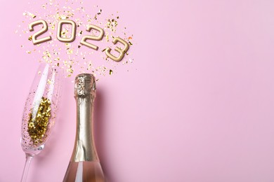 Bottle of sparkling wine, glass, golden confetti and number 2023 on pink background, flat lay with space for text. Happy New Year