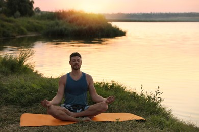 Man meditating near river in twilight. Space for text
