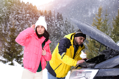 Stressed couple near broken car outdoors on winter day