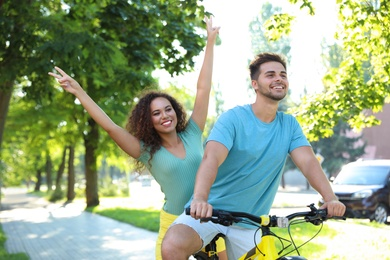 Happy young couple riding bicycle on city street