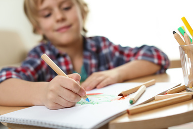 Little boy drawing at table indoors, focus on hand. Creative hobby