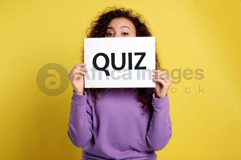 African American woman holding sign with word QUIZ on yellow background