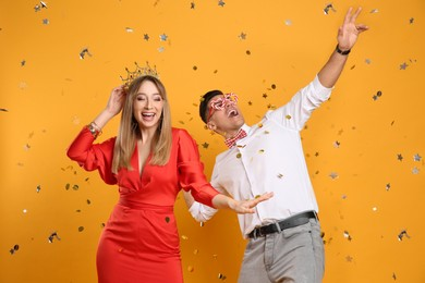 Happy couple and confetti on yellow background