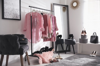 Dressing room interior with clothing rack and comfortable chair