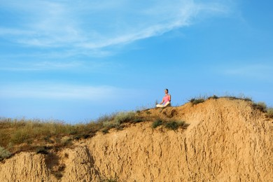 Distant view of woman meditating on sandy hill