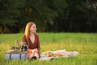 Beautiful young woman with picnic basket sitting on blanket in park