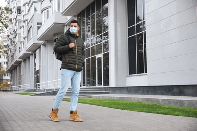 Man in medical face mask walking outdoors. Personal protection during COVID-19 pandemic