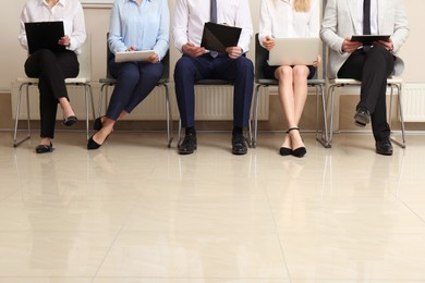 People waiting for job interview in office hall, closeup