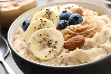 Tasty oatmeal porridge with toppings in bowl on table, closeup