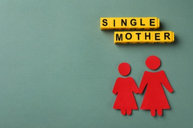 Being single mother concept. Woman with her child made of paper on grey background, flat lay and space for text