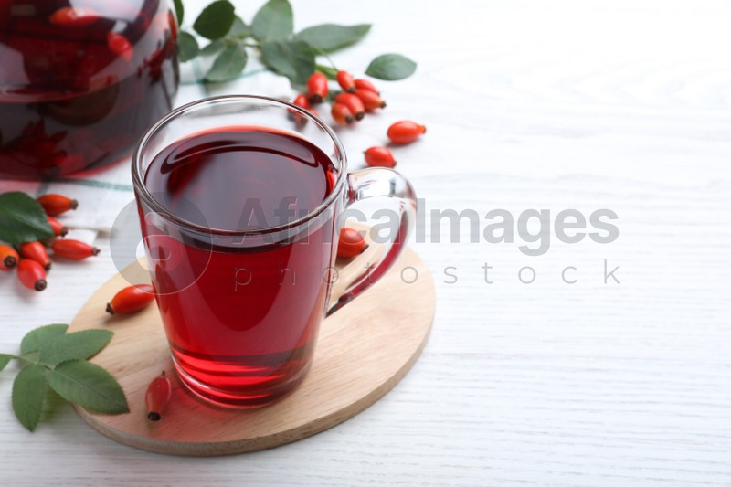 Aromatic rose hip tea and fresh berries on white wooden table, space for text