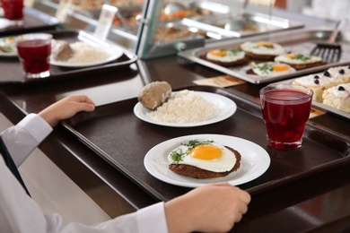 Girl near serving line with healthy food in school canteen, closeup