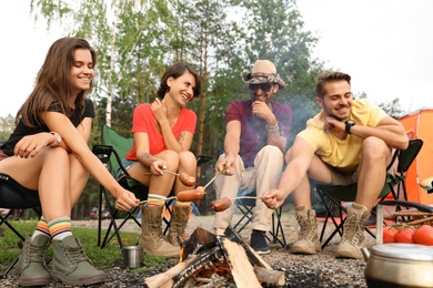 People having lunch with sausages near camping tent outdoors