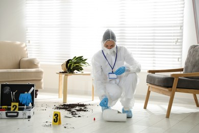 Investigator in protective suit working at crime scene indoors
