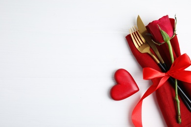 Top view of cutlery with napkin and decorative heart on white wooden table, space for text. Valentine's Day romantic dinner